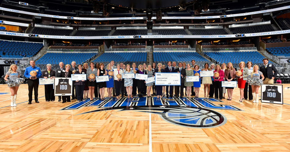OMYF Sponsors with checks on basketball court
